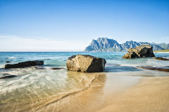 A view of the rocky beach Uttekleiv Lofoten. Blurry effect of water surface with long exposure Royalty Free Stock Photo