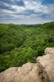 View from rocky cliff edge overlooking green valley and blue sky Stock Image