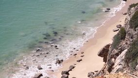 View from a rocky cliff towards incoming waves and the rocky beach. View from a rocky cliff in Portugal towards incoming waves and the rocky beach stock video footage