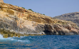 View of rocky sea coast, Malta. View of a rocky sea coast in Mediterranean area, yellowish rocks almost without plants, clear blue water of sea on foreground Royalty Free Stock Photo
