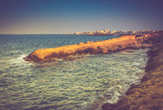 View of the rocky coast, foaming waves of the sea and the city in the distance at sunset. Stock Images