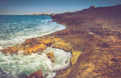 View of the rocky coast, foaming waves of the sea and the city in the distance at sunset. Stock Photography