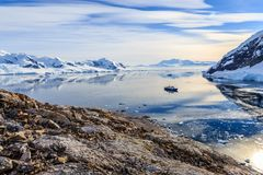 View from the rocky coast to the Neco bay surrounded by glaciers. And mountains and cruise ship standing still on the sea surface, Antarctic