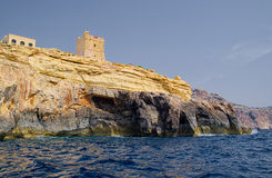 View of rocky coast, Malta. View of yellow rocky coast with some old tower on top, deep blue sea water on foreground Royalty Free Stock Photos