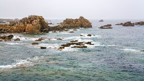 View of rocky coastline in Brittany in rainy day. Travel in France - view of rocky coastline of Gouffre gulf of English Channel near Plougrescant town of the Royalty Free Stock Image