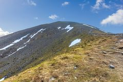 A view of a rocky Scottish mountain Ben Vorlich summit with rocky and grassy slope under a majestic blue sky and white clouds.  stock photo