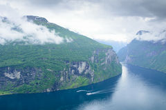 View of the rocky shore of Geiranger Fjord and waterfall.  Stock Image