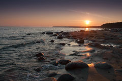 View of rocky shore at sunset. View of rocky shore showing high contrast sunset clouds and smooth wavy waters Royalty Free Stock Photos