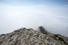 View from the rocky top of the mountain above the clouds Stock Photos