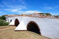Roman bridge and city buildings, Silves, Portugal. View of the Roman bridge across the river Arade with the Gothic cathedral, castle and town buildings to the Royalty Free Stock Images