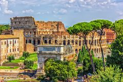 View from the Roman Forum on the Arch of Titus and the Colosseum, summer cloudy day stock photo