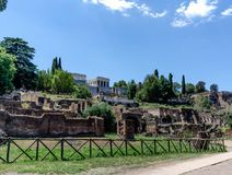 View of the Roman forum ruins with a very blue sky slightly clou. Dy Stock Photography