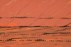View of a roof covered with corrugated iron plates painted red and rusted. royalty free stock photography