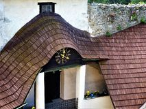 Fragment of the roof structure of the old castle with the clock royalty free stock photos