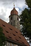 Augustiner-Chorherrenstift und Trinitatiskirche. View of the roof of a wing of the Augustiner-Chorherrenstift in Langenzenn, Germany, with the steeple of the Stock Images