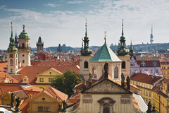 View of the roofs of Prague, with red tiled roofs and  statues, spires and towers protruding Royalty Free Stock Photo
