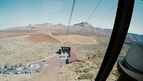 View from a ropeway cabin to mountains and station of departure. Cablecar moves up to the top of volcano. Traveling to mountain on the funicular stock video
