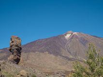 View on Roque Cinchado and colorful volcano pico del teide highe. St spanish mountain from famous rock formation Roques de Garcia with clear blue sky Royalty Free Stock Image