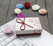 View of roses, white laptop and red gift box on background. royalty free stock image