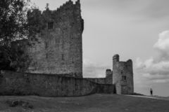 A view of Ross Castle from with a person in the distant to show the scale of the castle. On an overcast day royalty free stock photos