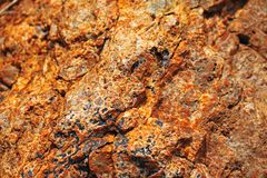 RED ROCK WITH BLACK DEPOSITS EMBEDDED IN FORMATION Stock Photography