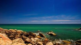 View Round Rock Stony Beach Azure Sea Skyline. Camera moves from round rock to stony beach along azure sea up to skyline waves splash stock video footage
