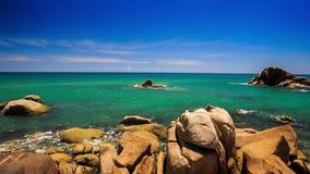 View Round Rock Stony Beach Azure Sea Skyline. Camera moves from round rock to stony beach along azure sea up to skyline waves splash stock video