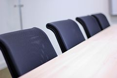 View of row of office chairs in a meeting room. Row of black office chairs in a meeting room with white board in the distance stock photo