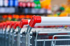 View of a row of push carts in a supermarket. Close up view of a row of push carts in a supermarket on the background of counters in blur Stock Image