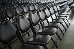 Rows of empty black folding chairs. View of rows of empty black folding chairs at an event Stock Photos