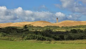 View of the Rubjerg Knude. High sand dune at the west coast of Denmark. Old lighthouse partly covered by sand. Old lighthouse and Rubjerg Knude Stock Photo