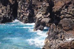 View on rugged rough coastline with sharp cliffs. lagoon with turquoise blue water, waves - Los Hervidereos, Lanzarote stock image