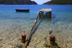View of a ruined wooden pier and an old fishing boat and mountains in the background of sithonia Greece Royalty Free Stock Images