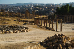 View ruins Oval Forum and long colonnaded street or cardo ancient Greco-Roman city Gerasa. Modern Jerash on background. Tourism in Stock Image