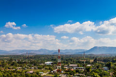 View of rural areas, antenna of communication and cloud. View of landscape rural areas, antenna of communication building and cloud on blue sky Stock Image