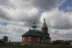 View of the rural church under the blue sky with white clouds in  Russia. View of the rural church under the blue sky with white clouds in Chuvashia, Russia stock images