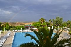 A view of a rural landscape, swimming pool and rainbow stock images