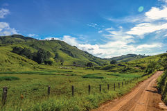 View of rural road next to green hills near the town of Joanópolis. royalty free stock image
