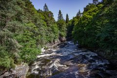 View of a rushing stream, forest and small cottage in Invermoriston Stock Photography
