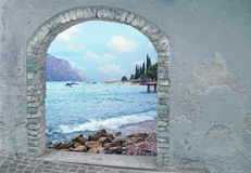 View through rustic vintage door, mountain lake and mediterranea Royalty Free Stock Photography