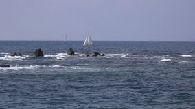 Sailboat near dangerous jagged rocks along coast. View of sailboat near dangerous jagged rocks along Tel Aviv coast stock footage