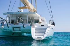 Sailing catamaran in blue waters of the Aegean sea. View of a sailing catamaran in the blue waters of the Aegean sea, Greece Stock Photos