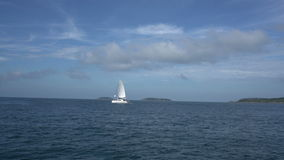 View of sailing yacht in sea and islands far away. View of sailing yacht in sea and tropical islands far away stock footage