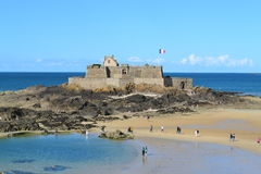 A view of Saint Malo Castle in the mid tide, France. People crossing the mid tide to reach Saint Malo castle, west cost of France Stock Photography
