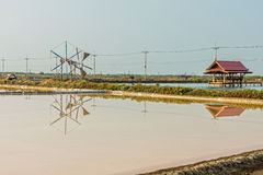 View of salt evaporation pond and wind wheel and pavilion Stock Photo