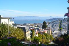 View of San Francisco Bay and Historic Homes. Scenic view from the top of crooked Lombard Street in San Francisco, California of the SF Bay and historic Royalty Free Stock Images