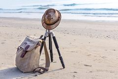 View of the sandy beach with a brown hat and knapsack on the bea. Ch near the sea. The swash of seawater up the beach after the breaking of a wave. Background Royalty Free Stock Image