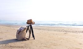 View of the sandy beach with a brown hat and knapsack on the bea. Ch near the sea. The swash of seawater up the beach after the breaking of a wave. Background Royalty Free Stock Images