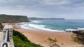 View of the sandy beach in cloudy foggy day Stock Image