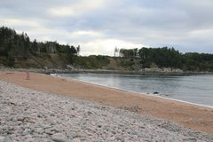 A view of a sandy beach with a lifeguard chair on the sand. The beach is ringed by beach stones.  There is a forested cliff in the background, beautiful, blue royalty free stock images